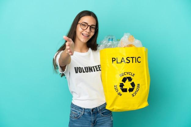 Jovem francesa segurando uma sacola cheia de garrafas plásticas para reciclar apertando as mãos para fechar um bom negócio