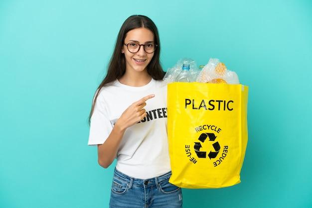 Jovem francesa segurando uma sacola cheia de garrafas plásticas para reciclar apontando para o lado para apresentar um produto