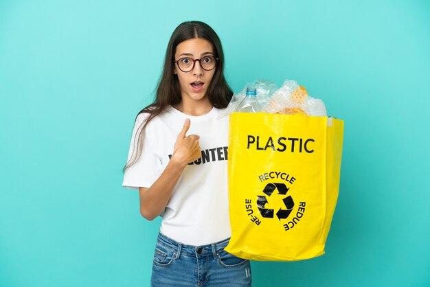 Jovem francesa segurando uma sacola cheia de garrafas plásticas para reciclar com expressão facial surpresa
