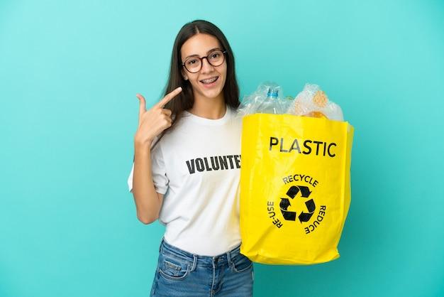 Jovem francesa segurando uma sacola cheia de garrafas plásticas para reciclar e fazendo um gesto de polegar para cima