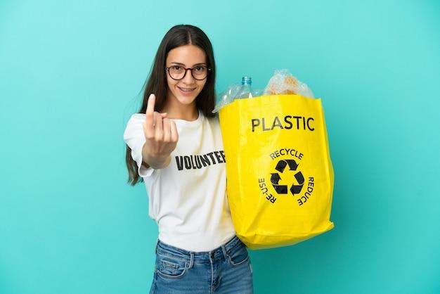 Jovem francesa segurando uma sacola cheia de garrafas plásticas para reciclar fazendo gesto de vir