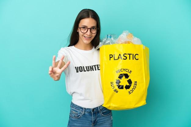 Jovem francesa segurando uma sacola cheia de garrafas plásticas para reciclar feliz e contando três com os dedos