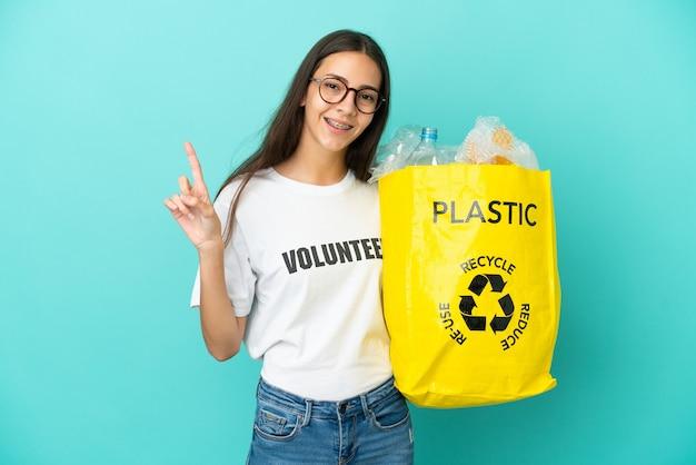 Jovem francesa segurando uma sacola cheia de garrafas plásticas para reciclar, mostrando e levantando um dedo em sinal dos melhores
