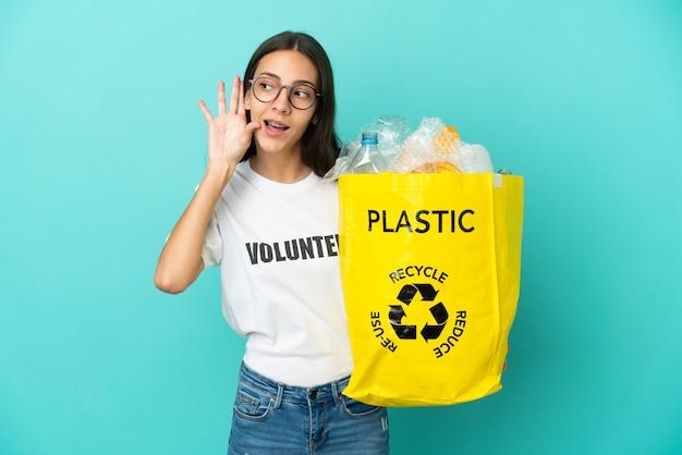 Jovem francesa segurando uma sacola cheia de garrafas plásticas para reciclar ouvindo algo colocando a mão na orelha