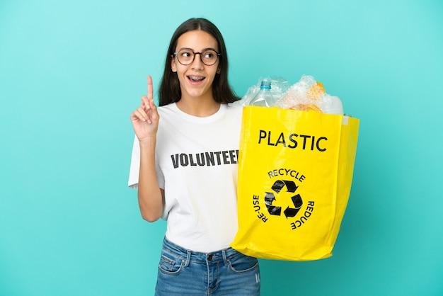 Jovem francesa segurando uma sacola cheia de garrafas plásticas para reciclar pensando em uma ideia apontando o dedo para cima