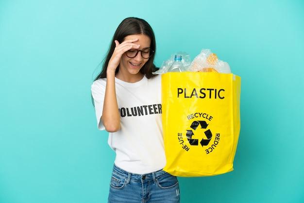 Jovem francesa segurando uma sacola cheia de garrafas plásticas para reciclar rindo