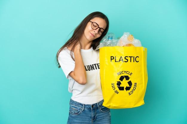 Jovem francesa segurando uma sacola cheia de garrafas plásticas para reciclar sofrendo de dores no ombro por ter feito um esforço