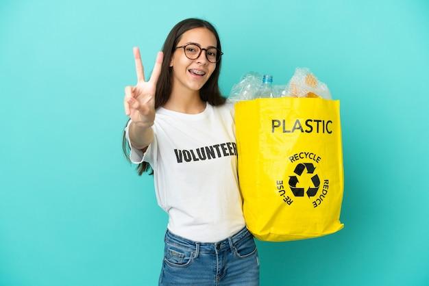 Jovem francesa segurando uma sacola cheia de garrafas plásticas para reciclar sorrindo e mostrando o sinal da vitória