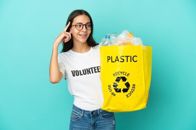 Jovem francesa segurando uma sacola cheia de garrafas plásticas para reciclar, tendo dúvidas e pensando