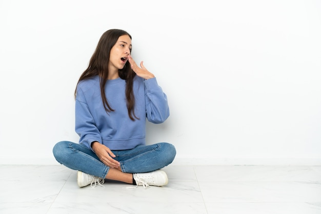 Jovem francesa sentada no chão, bocejando e cobrindo a boca aberta com a mão