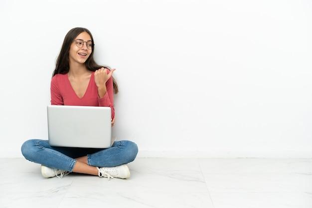 Jovem francesa sentada no chão com seu laptop apontando para o lado para apresentar um produto