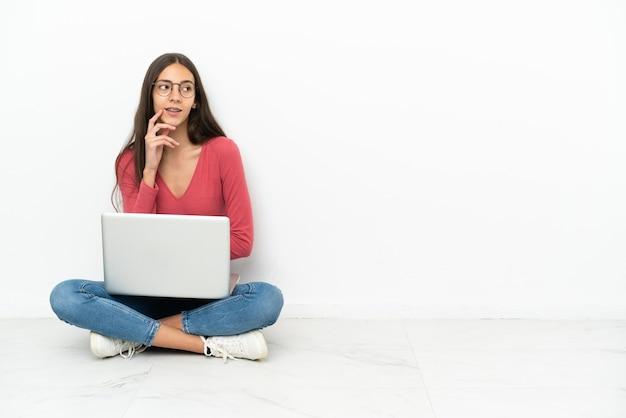Jovem francesa sentada no chão com seu laptop pensando em uma ideia enquanto olha para cima