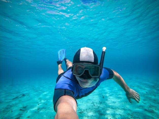 Jovem freediver tomando selfie retrato debaixo d'água, ponto de vista.