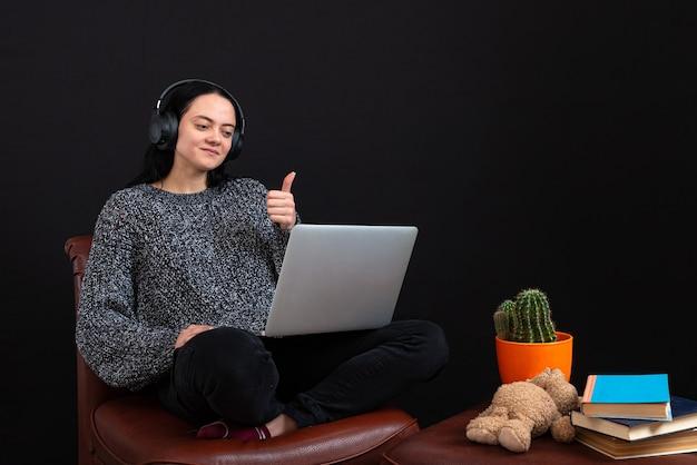 Jovem freelance focada, sentada com laptop e fones de ouvido, tendo uma reunião de negócios por videochamada