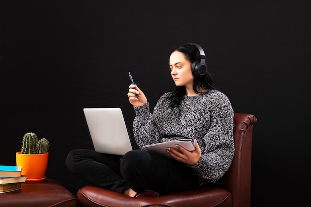 Jovem freelance focada, sentada com um laptop e fones de ouvido, trabalhando remotamente online em casa