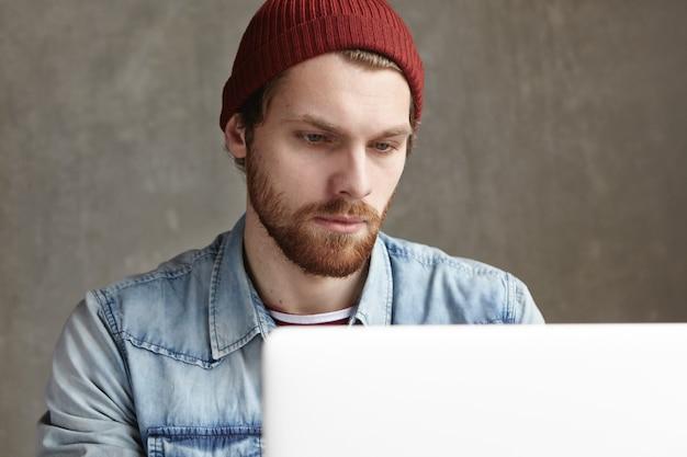 Jovem freelancer barbudo caucasiano vestido com roupas elegantes, sentado em um café