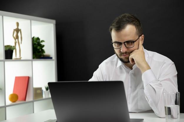 Jovem freelancer bonito trabalhando no laptop em casa durante o auto-isolamento