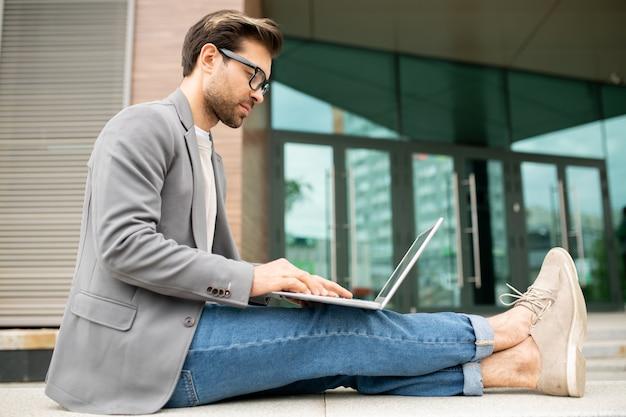 Jovem freelancer casual sentado em um prédio moderno com o laptop sobre os joelhos enquanto navega na internet ou trabalha em um projeto