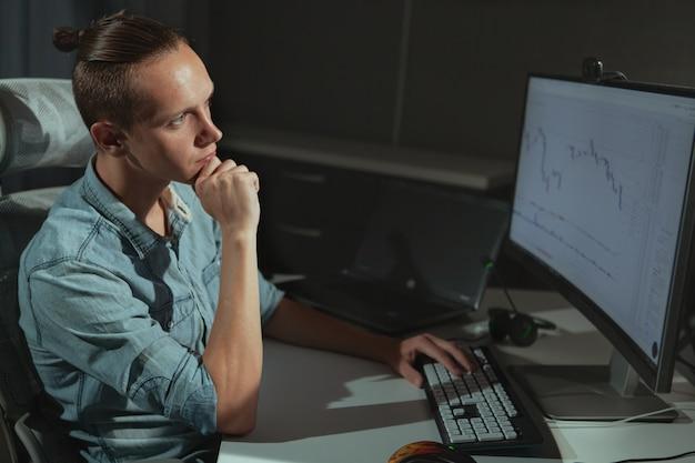 Jovem freelancer de indústria de ti masculino trabalhando tarde da noite