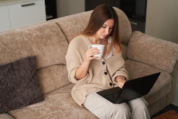 Jovem freelancer em casa no sofá, trabalhando em um laptop e bebendo café