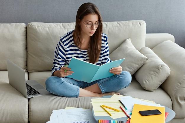 Jovem freelancer faz trabalhos de dança em casa, estuda, senta-se de pernas cruzadas no sofá
