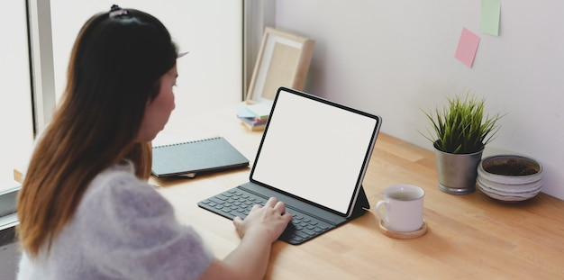Jovem freelancer feminino trabalhando em seu projeto com tablet