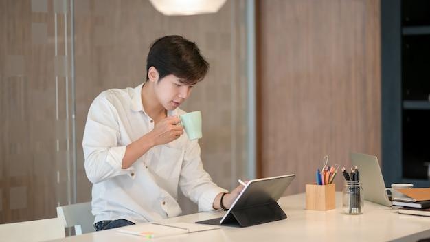Jovem freelancer masculino bonito tomando um café enquanto trabalhava em seu projeto