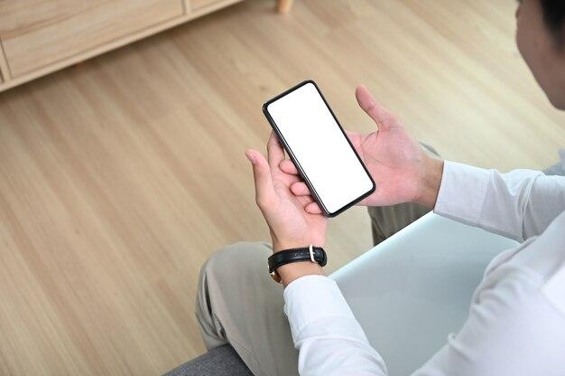 Jovem freelancer masculino segurando o telefone enquanto olha para a tela, assistindo às mídias sociais no sofá.