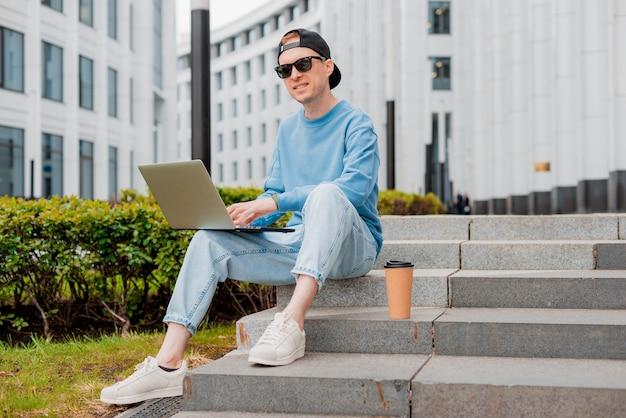 Jovem freelancer masculino sorridente com roupa moderna sentado do lado de fora na escada com laptop e café para viagem