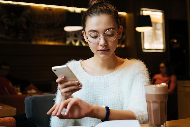 Jovem freelancer ocupada com uma jaqueta branca e óculos sentada em um café, olhando para um relógio de pulso, segurando um smartphone na mão