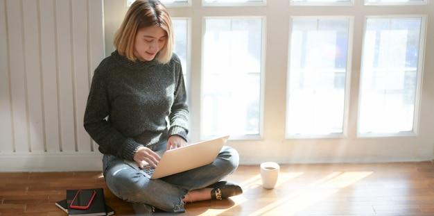 Jovem freelancer profissional trabalhando em seu projeto enquanto está sentado perto das janelas