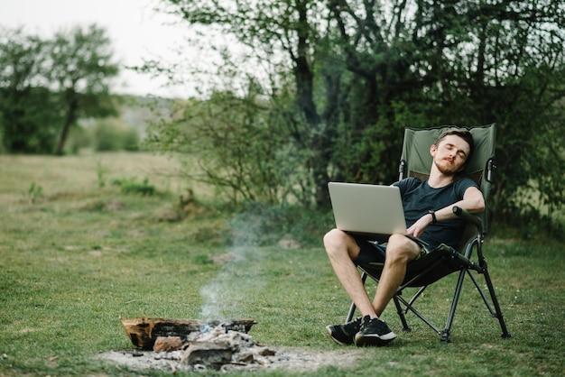 Jovem freelancer relaxando na floresta