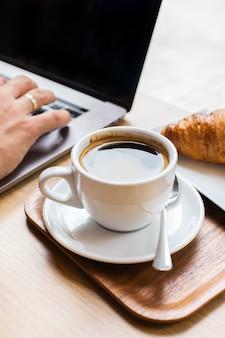 Jovem, freelancer, sentado em um café, bebendo café e trabalhando em um laptop. composição de estilo de vida com luz natural