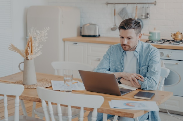 Jovem freelancer sério e focado trabalhando em um laptop enquanto está sentado à mesa da cozinha com as mãos apoiadas nele, gráficos e estatísticas espalhados ao redor, abra o caderno ao lado dele