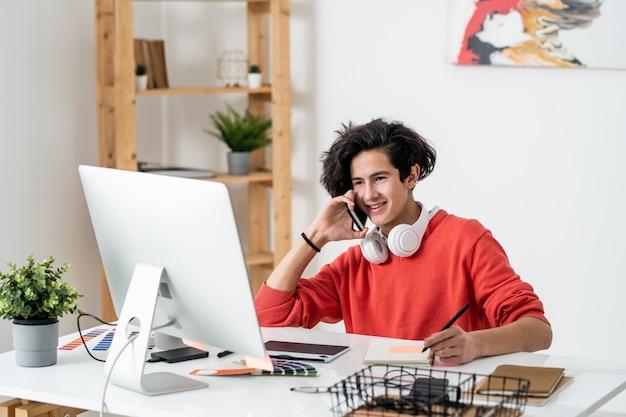 Jovem freelancer sorridente falando em um smartphone enquanto está sentado à mesa na frente do computador e retocando fotos