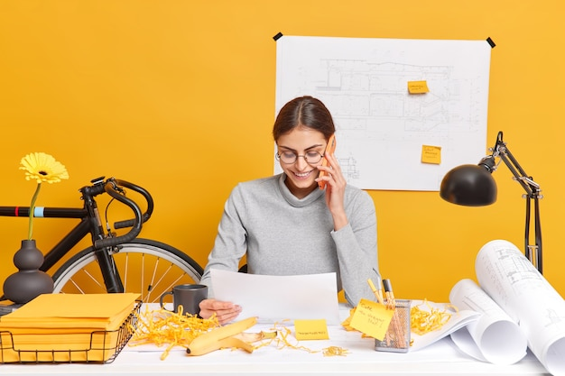 Jovem freelancer trabalha em casa, conversa por telefone com foco em documento em papel, discute futuras consultas de projetos com líderes profissionais qualificados por meio de poses de smartphone no desktop