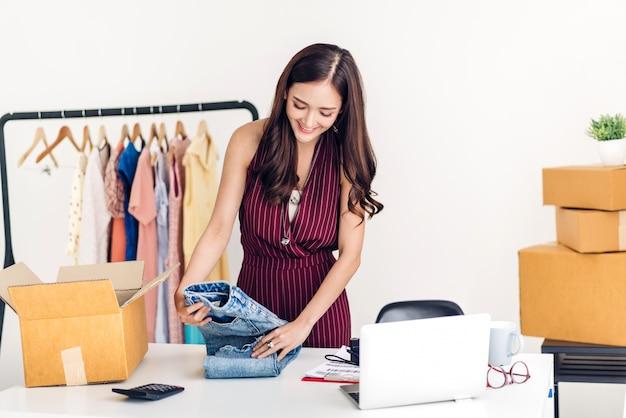 Jovem freelancer trabalhando sme negócios compras on-line e embalagem de roupas com caixa de papelão em casa - conceito de transporte e entrega on-line de negócios
