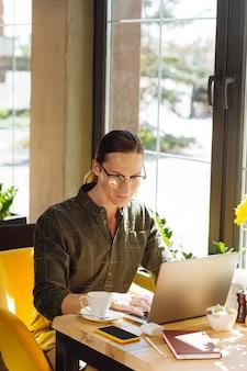 Jovem freelancer. vista superior de um jovem positivo sorrindo enquanto trabalhava como freelancer em um café
