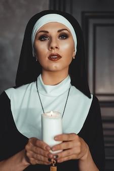 Jovem freira católica está segurando uma vela nas mãos. foto em fundo preto. retrato de mulher bonita