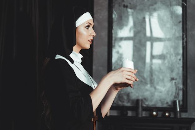 Jovem freira católica está segurando uma vela nas mãos. foto em fundo preto. vista lateral.