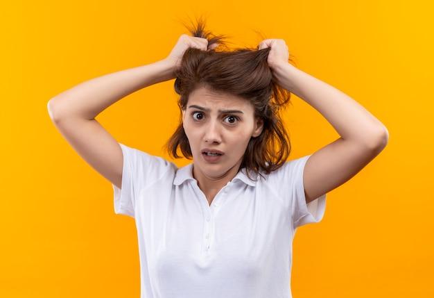 Jovem frustrada com cabelo curto, usando uma camisa pólo branca, estressada e confusa puxando o cabelo
