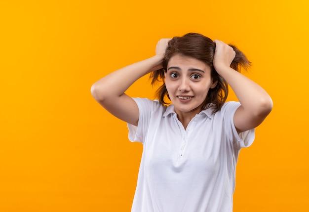 Jovem frustrada com cabelo curto, usando uma camisa pólo branca puxando o cabelo