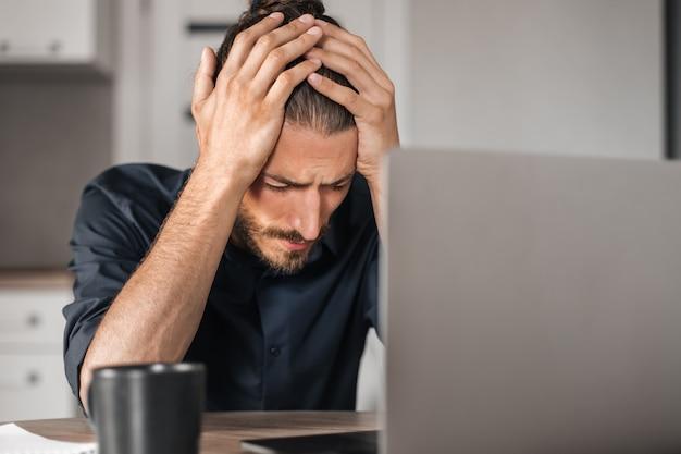Jovem frustrado trabalhando em um laptop
