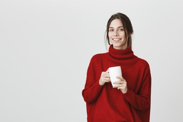 Jovem funcionária bebendo café, segurando a caneca e sorrindo