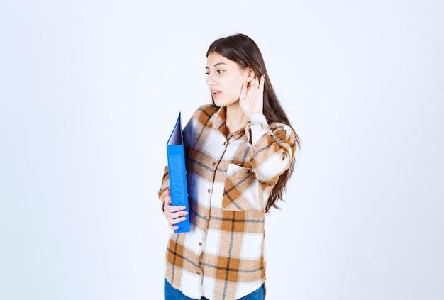 Jovem funcionário com pasta azul, tentando ouvir algo na parede branca.