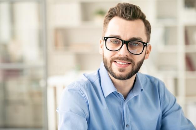 Jovem funcionário de sucesso com óculos e camisa azul sentado no escritório