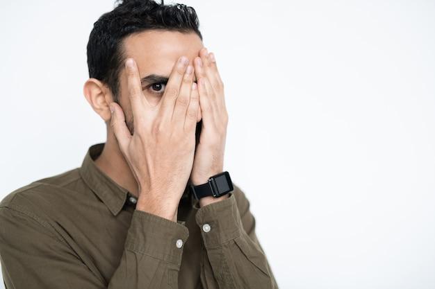 Jovem funcionário mestiço cobrindo o rosto com as mãos e olhando para você por um olho entre os dedos