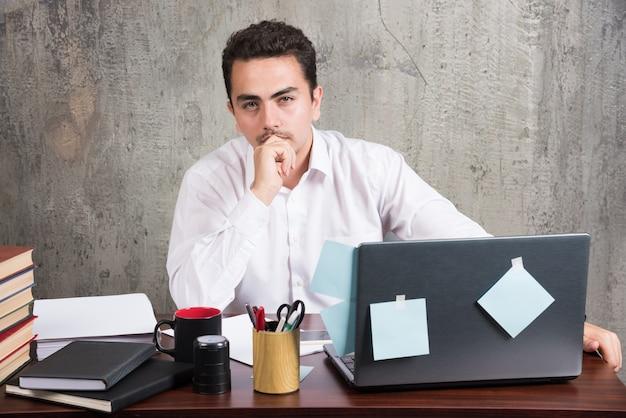 Jovem funcionário olhando a câmera para a mesa do escritório.
