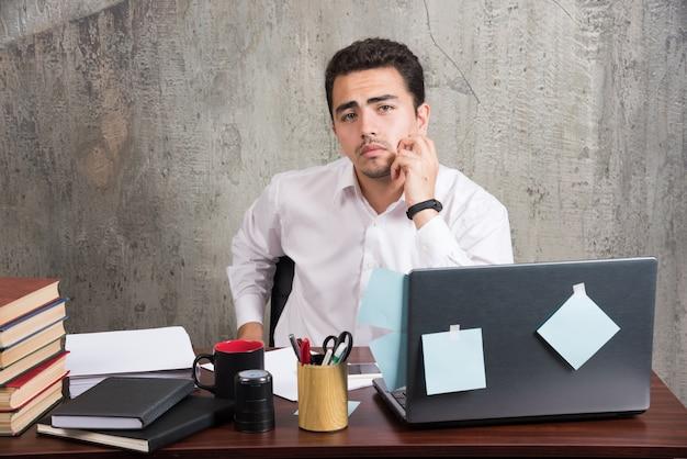 Jovem funcionário posando na mesa do escritório.