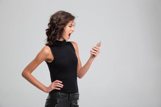 Jovem furiosa gritando e usando telefone celular